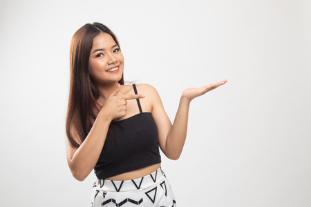 Beautiful young Asian woman point to palm hand on white background Banco de Imagens
