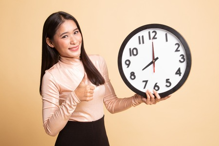 Young Asian woman thumbs up with a clock on  beige background