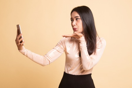 Young Asian woman with mobile phone on  beige background