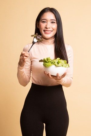 Healthy Asian woman with salad on  beige background 版權商用圖片