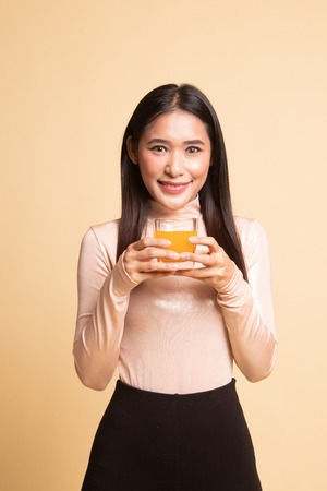 Young Asian woman drink orange juice on  beige background