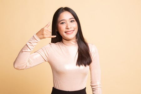 Young Asian woman show with phone gesture on  beige background
