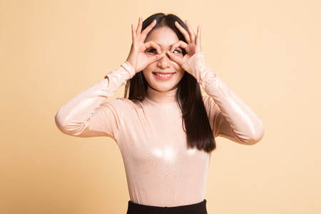 Asian woman do funny  double OK sign as glasses on  beige background