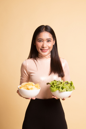 Young Asian woman with potato chips and salad on  beige background 版權商用圖片