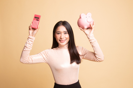 Asian woman with calculator and piggy bank on  beige background