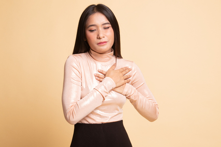 Young Asian woman got chest pain on  beige background