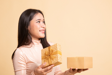 Young Asian woman open a gift box on  beige background Stockfoto - 122885078