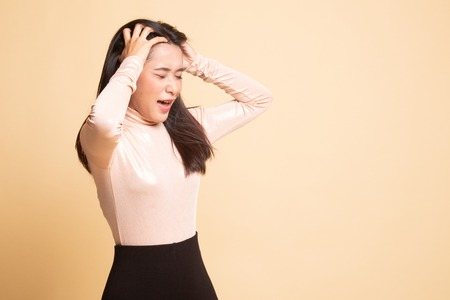 Stressed young Asian businesswoman scream out on  beige background