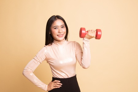 Healthy Asian woman with dumbbells on  beige background