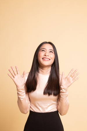 Excited young Asian woman look up on  beige background 版權商用圖片