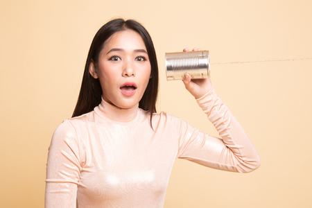 Surprised young Asian woman with tin can phone on  beige background