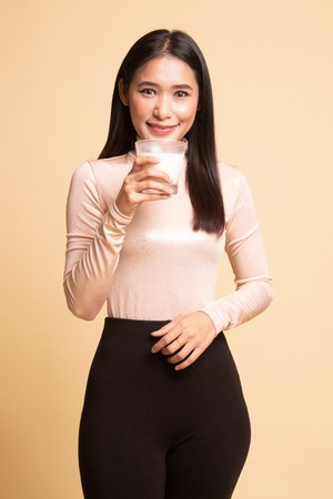 Healthy Asian woman drinking a glass of milk on  beige background
