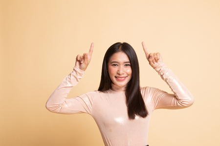 Young Asian woman point to blank space on  beige background 版權商用圖片