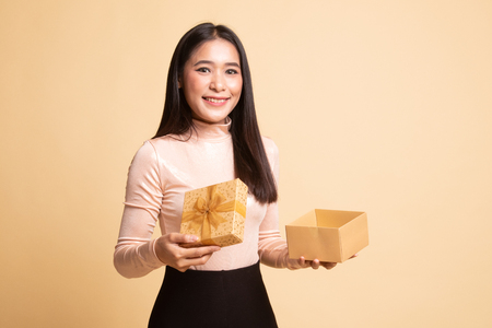 Young Asian woman open a golden gift box on  beige background