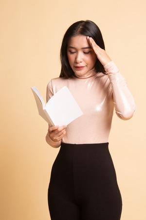 Young Asian woman got headache read a book on  beige background 版權商用圖片