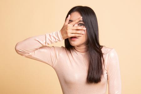 Beautiful young Asian woman peeking through fingers on  beige background 版權商用圖片
