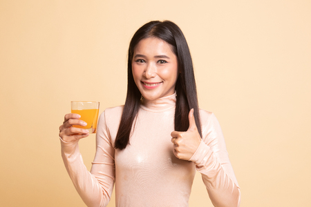 Young Asian woman thumbs up drink orange juice on  beige background