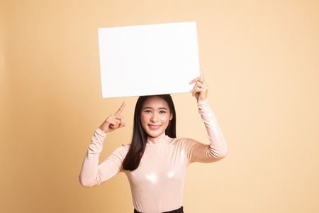 Young Asian woman point to blank sign on  beige background