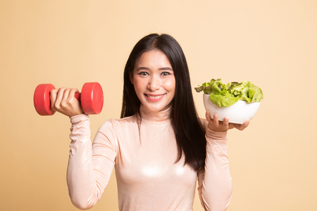 Healthy Asian woman with dumbbells and salad on  beige background