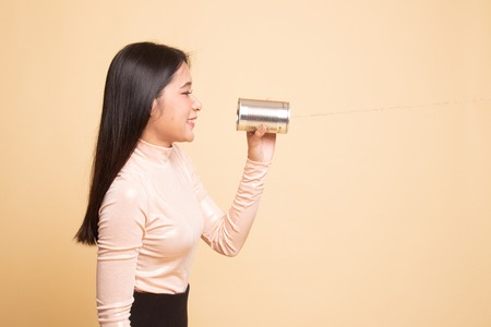 Young Asian woman with tin can phone on  beige background