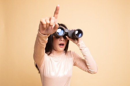 Young Asian woman  point and look with binoculars on  beige background