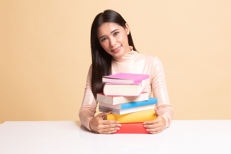 Happy young Asian woman read a book with books on table on  beige background