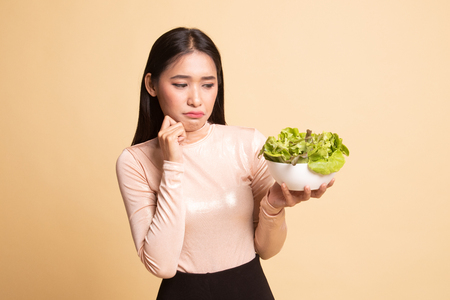 Asian woman hate salad on  beige background