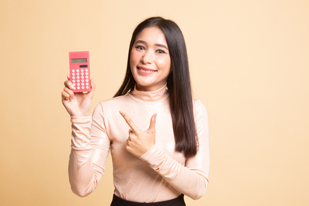 Asian woman point to  calculator on  beige background