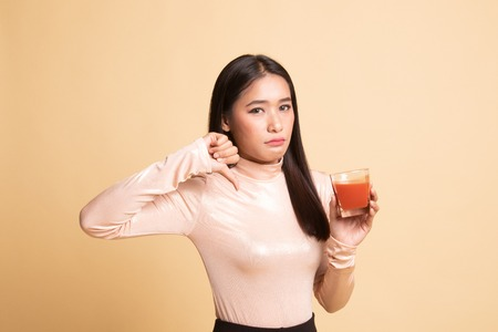 Young Asian woman  thumbs down hate tomato juice on  beige background 版權商用圖片
