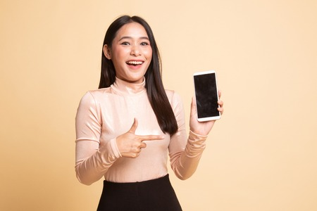 Excited Young Asian woman point to mobile phone on  beige background
