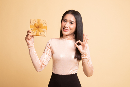 Young Asian woman show OK with a gift box on  beige background