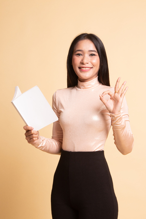Young Asian woman show OK with a book on  beige background