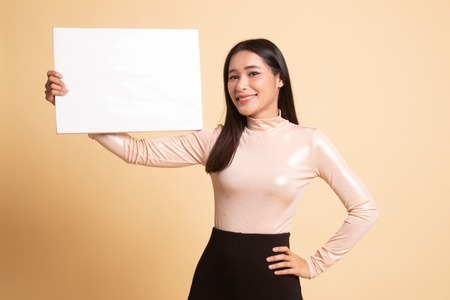 Young Asian woman with white blank sign on  beige background 版權商用圖片