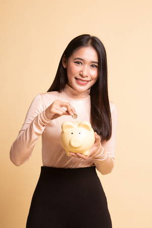 Asian woman with coin and pig coin bank on  beige background