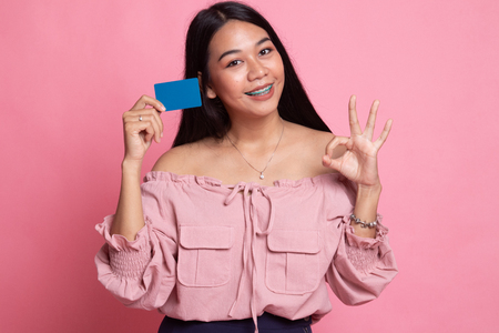 Young Asian woman show OK with a blank card on pink background Banco de Imagens
