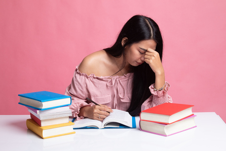 Exhausted Asian woman got headache read a book with books on table on pink background