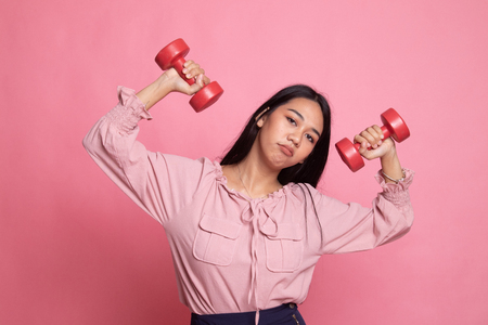 Exhausted Asian woman with dumbbells on pink background