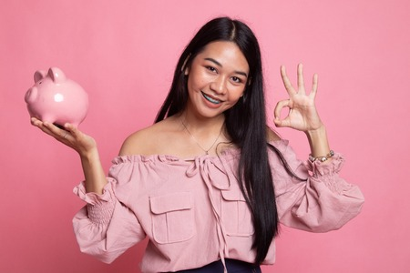 Asian woman show OK  with pig coin bank on pink background