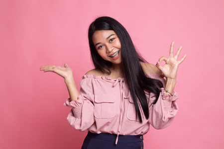 Beautiful young Asian woman show palm hand and OK sign on pink background