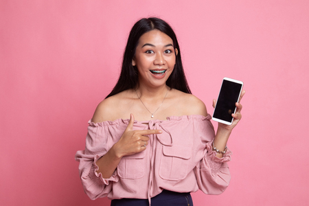 Excited Young Asian woman point to mobile phone on pink background Banco de Imagens