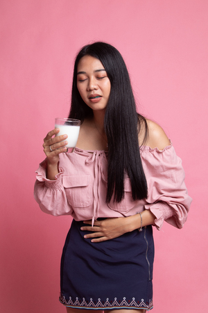 Asian woman drinking a glass of milk got stomachache on pink background
