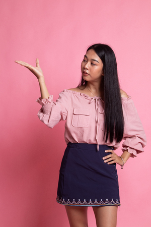 Young Asian woman present with her hand on pink background