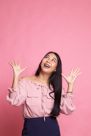 Excited young Asian woman look up on pink background