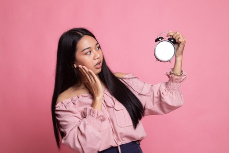 Young Asian woman is stressed with a clock on pink background