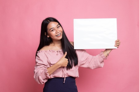 Young Asian woman show thumbs up with  white blank sign on pink background