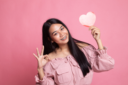 Asian woman show OK with red heart on pink background