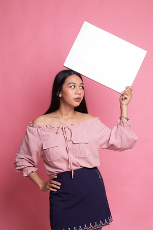 Young Asian woman with white blank sign on pink background