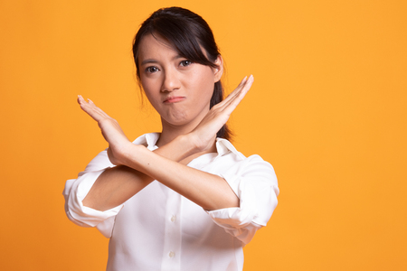 Beautiful young Asian woman say no on yellow background