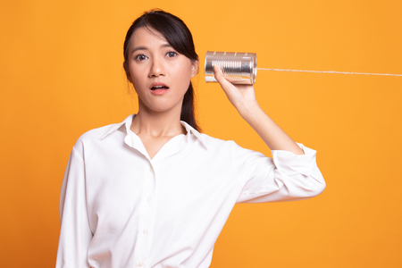 Surprised young Asian woman with tin can phone on yellow background