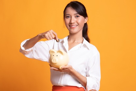 Asian woman with coin and pig coin bank on yellow background Banco de Imagens
